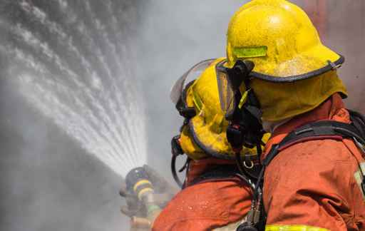 two firemen in helmet and oxygen mask spraying water to fire su_257870