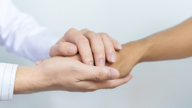Two People Holding Hands For Comfort. Doctor Consoling Relatives_1528481071975