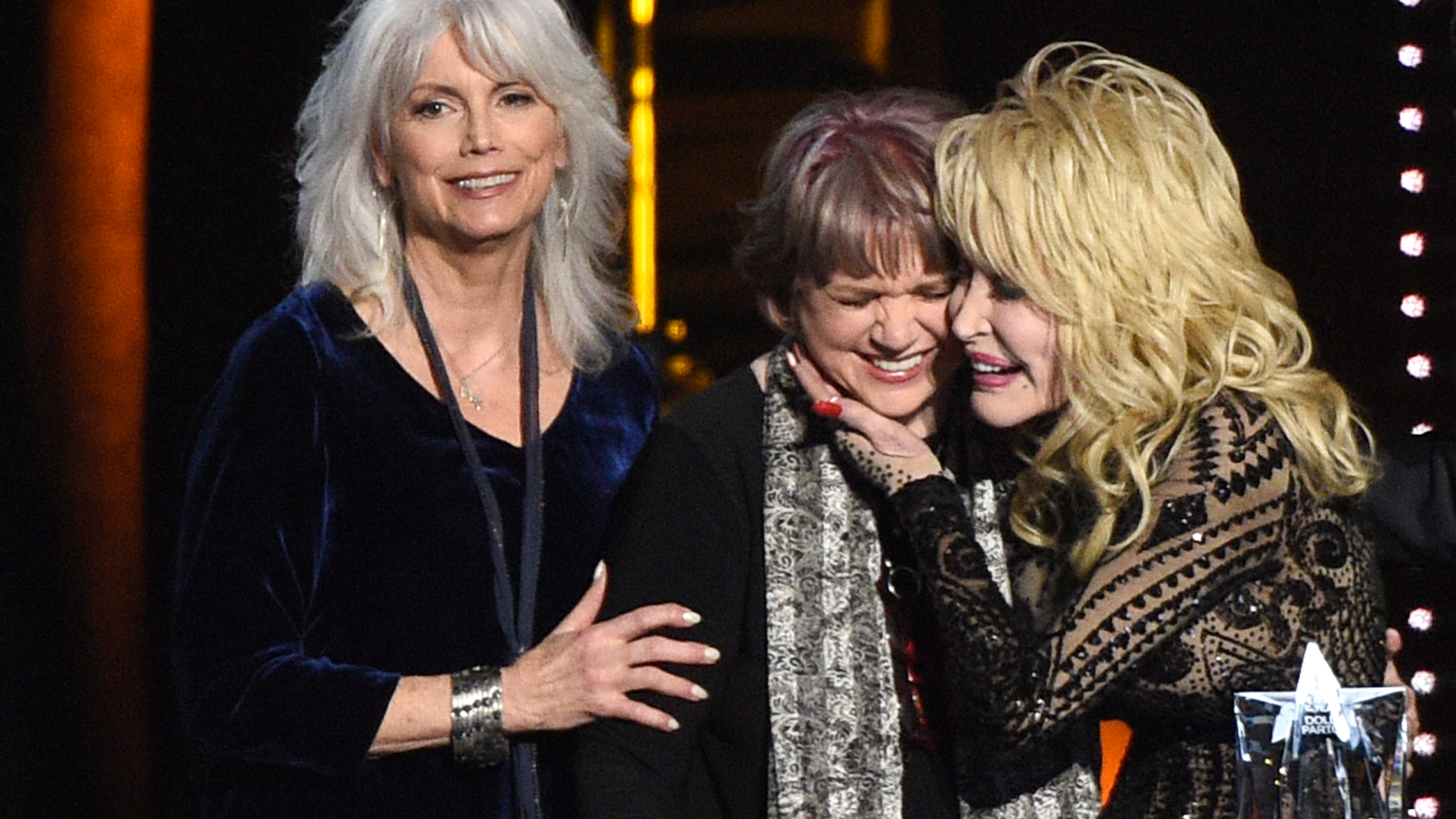 Emmylou Harris, from left, and Linda Ronstadt present Dolly Parton with the MusiCares Person of the Year