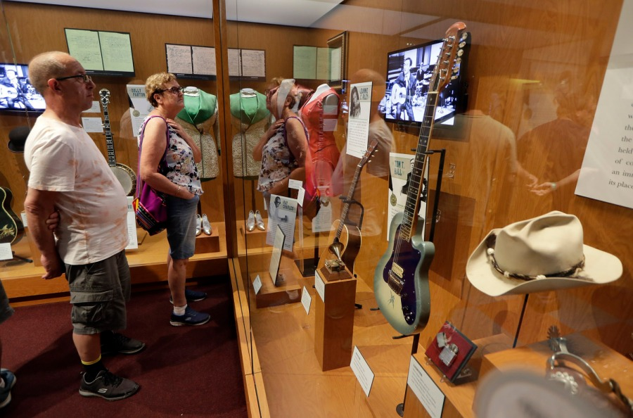 In this May 25, 2018 photo, visitors to the Country Music Hall of Fame and Museum in Nashville, Tenn., view the the Outlaws & Armadillos exhibit. The exhibit focuses on the music of the era that was driven by artists rather than labels. (AP Photo/Mark Humphrey)